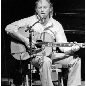 Stephen Stills on stage playing a guitar